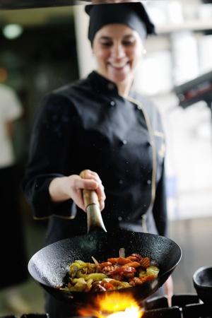 hermosa mujer joven chef prepare y sabrosa comida en la cocina de la decoración