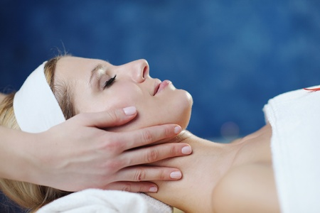 skincare: Beautiful young woman in spaand wellness. Face back and  stone massage
