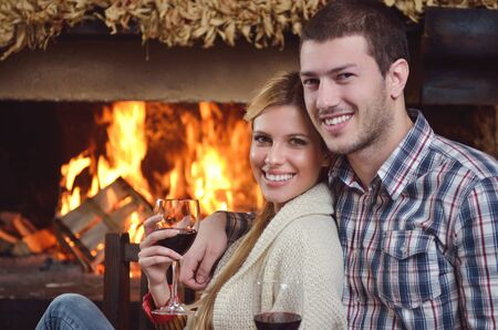 fireplace home: happy Young romantic couple and relaxing sofa in front of fireplace at winter season in home
