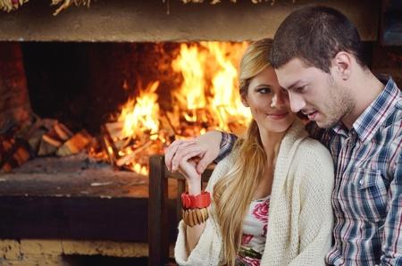 coppia in casa: giovane coppia felice romantico e rilassante divano davanti al camino in inverno in casa Archivio Fotografico