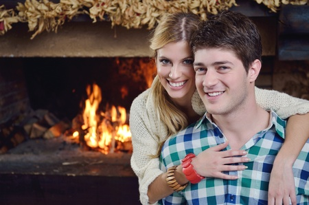 happy Young romantic couple and relaxing sofa in front of fireplace at winter season in home Stock Photo - 13487795