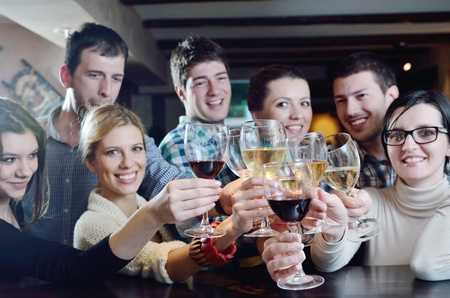 Group of happy young people drink wine  at party disco restaurant photo