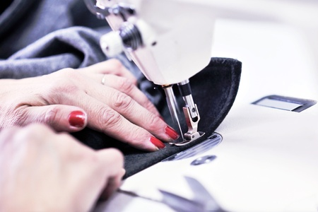 making dresses: woman Hands of Seamstress Using Sewing Machine tailor and new clothes fahion reparation concept Stock Photo