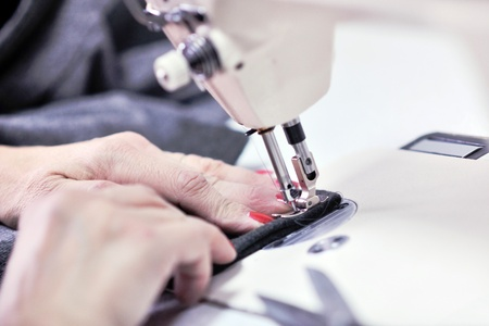 woman Hands of Seamstress Using Sewing Machine tailor and new clothes fahion reparation concept photo