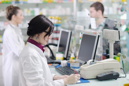 young pharmacist suggesting medical drug to buyer in pharmacy drugstore Stock Photo