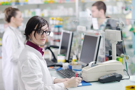 suggesting: young pharmacist suggesting medical drug to buyer in pharmacy drugstore Stock Photo