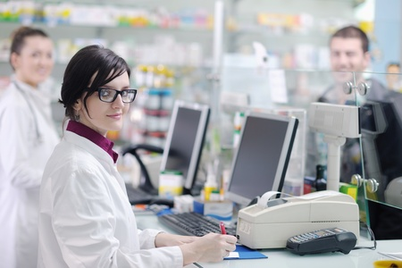 pharmacy store: young pharmacist suggesting medical drug to buyer in pharmacy drugstore Stock Photo