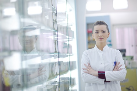 Happy cheerful pharmacist chemist woman standing in pharmacy drugstore photo