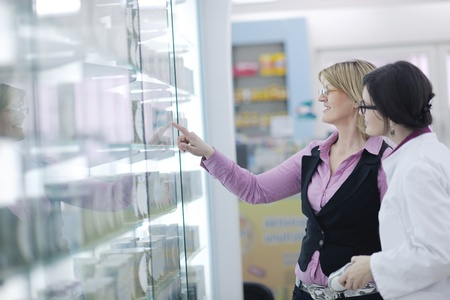 young pharmacist suggesting medical drug to buyer in pharmacy drugstore Stock Photo - 13578949