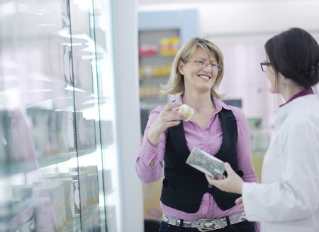 young pharmacist suggesting medical drug to buyer in pharmacy drugstore Stock Photo - 13582428