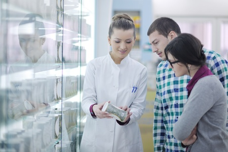 young pharmacist suggesting medical drug to buyer in pharmacy drugstore Stock Photo - 13578427