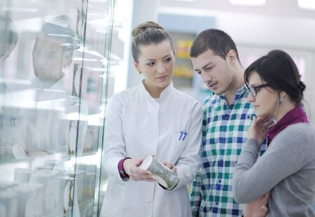 young pharmacist suggesting medical drug to buyer in pharmacy drugstore Stock Photo - 13582956