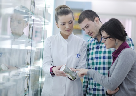 young pharmacist suggesting medical drug to buyer in pharmacy drugstore Stock Photo - 13583005