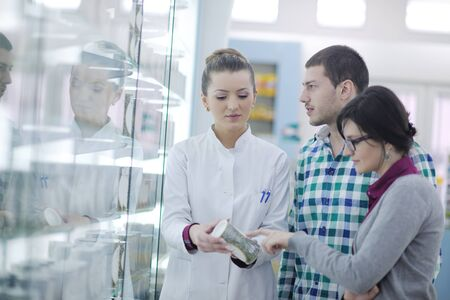 young pharmacist suggesting medical drug to buyer in pharmacy drugstore photo