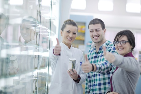 young pharmacist suggesting medical drug to buyer in pharmacy drugstore Stock Photo - 13579036