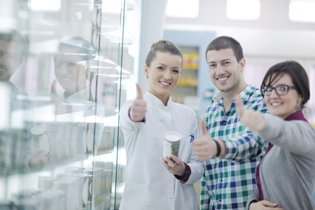 young pharmacist suggesting medical drug to buyer in pharmacy drugstore Stock Photo - 13579069