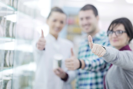 young pharmacist suggesting medical drug to buyer in pharmacy drugstore Stock Photo - 13578498