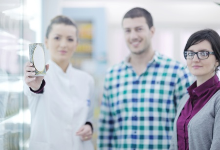 young pharmacist suggesting medical drug to buyer in pharmacy drugstore Stock Photo - 13579398
