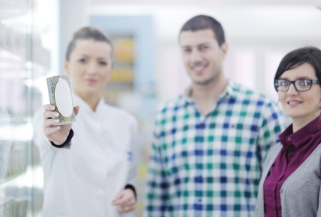 young pharmacist suggesting medical drug to buyer in pharmacy drugstore Stock Photo - 13582777