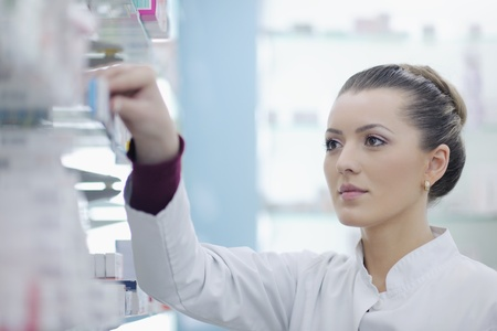 Happy cheerful pharmacist chemist woman standing in pharmacy drugstore photo