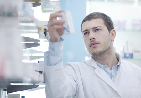 pharmacy store: portrait of handsome young  pharmacist chemist man standing in pharmacy drugstore