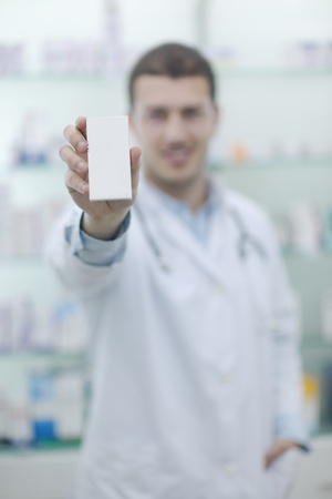 portrait of handsome young  pharmacist chemist man standing in pharmacy drugstore photo