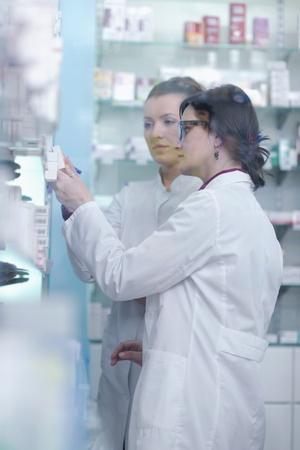team of  pharmacist chemist woman group  standing in pharmacy drugstore photo