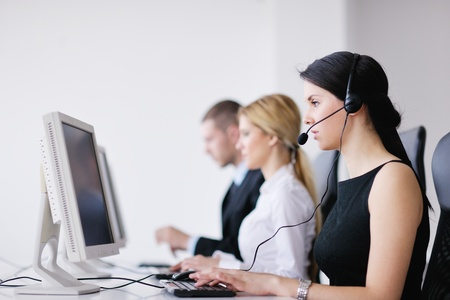 service center: business people group with  headphones giving support in  help desk office to customers, manager giving training and education instructions Stock Photo