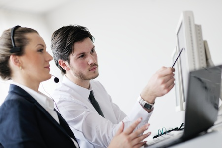 telemarketing: business people group with  headphones giving support in  help desk office to customers, manager giving training and education instructions Stock Photo