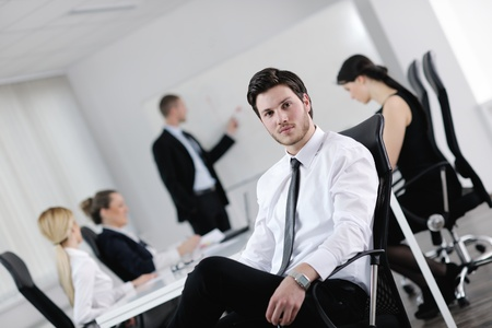 Portrait of a handsome young business man with people  in background at office meeting Stock Photo - 13581870