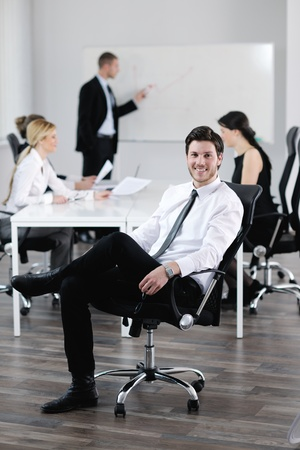 Portrait of a handsome young business man with people  in background at office meeting Stock Photo - 13578086