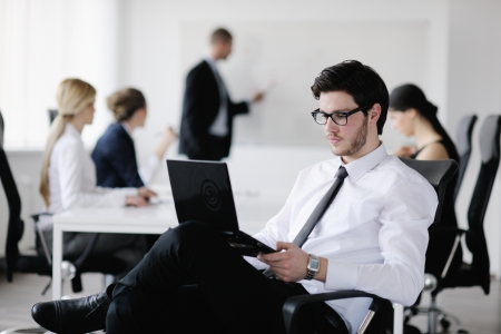 young office workers: Portrait of a handsome young business man with people  in background at office meeting Stock Photo