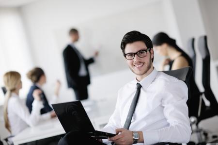 Portret van een knappe jonge zakenman met mensen op de achtergrond op kantoor vergadering Stockfoto