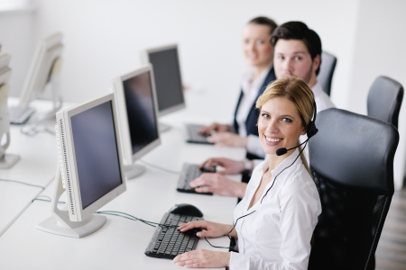 contact center: business people group with  headphones giving support in  help desk office to customers, manager giving training and education instructions Stock Photo