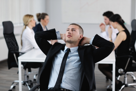Portrait of a handsome young business man with people  in background at office meeting Stock Photo - 13628703