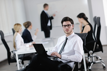 Portrait of a handsome young business man with people  in background at office meeting photo