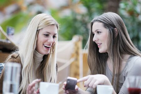 heel schattig glimlachende vrouwen het drinken van een kopje koffie zit binnen in cafe-restaurant