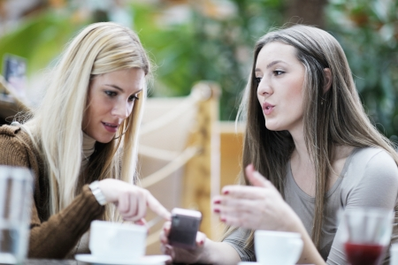very cute smiling women drinking a coffee sitting inside in cafe restaurant photo