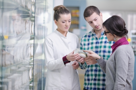 young pharmacist suggesting medical drug to buyer in pharmacy drugstore Stock Photo - 13661813