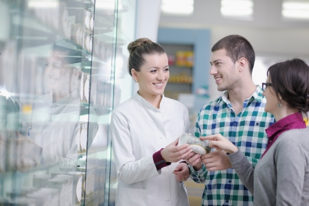 young pharmacist suggesting medical drug to buyer in pharmacy drugstore Stock Photo - 13661796