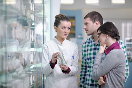 young pharmacist suggesting medical drug to buyer in pharmacy drugstore Stock Photo - 13656151