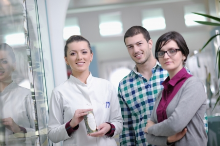 young pharmacist suggesting medical drug to buyer in pharmacy drugstore Stock Photo - 13661792