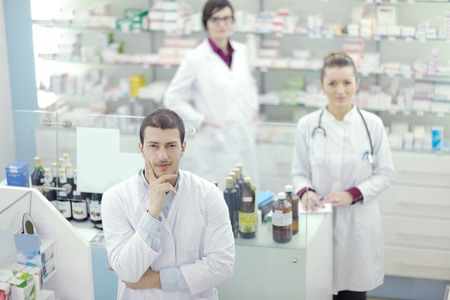 medical education: team of  pharmacist chemist woman and man  group  standing in pharmacy drugstore Stock Photo