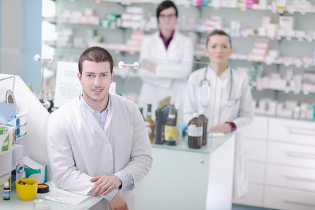 team of  pharmacist chemist woman and man  group  standing in pharmacy drugstore photo