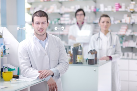 drug store: team of  pharmacist chemist woman and man  group  standing in pharmacy drugstore Stock Photo
