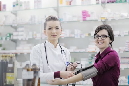 doctor checking blood pressure and heart rate in a hospital or in pharmacy with young female patient photo