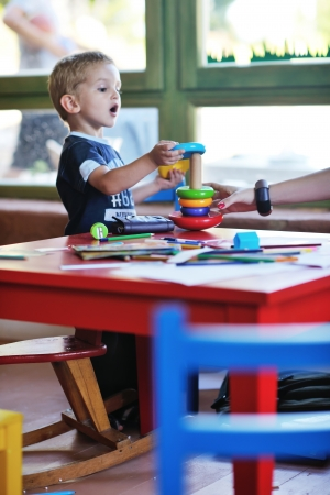 jardin de infantes: feliz de pequeño juego un juego de niños y se divierten, las clases de educación en el área de juegos de colores en el interior del jardín kinder
