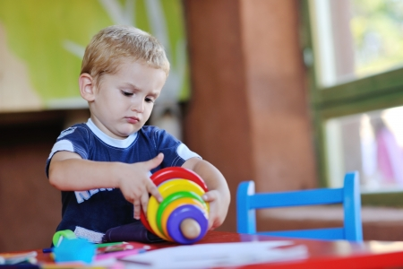 play room: happy little child play game and have fun, education lessons in colorful kinder garden playground indoors Stock Photo