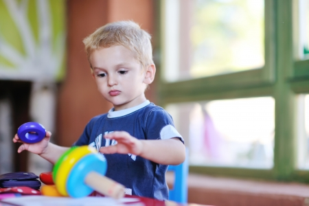 kids class: happy little child play game and have fun, education lessons in colorful kinder garden playground indoors Stock Photo