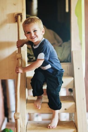 niño hermoso que los primeros pasos y se divierten en el patio de recreo